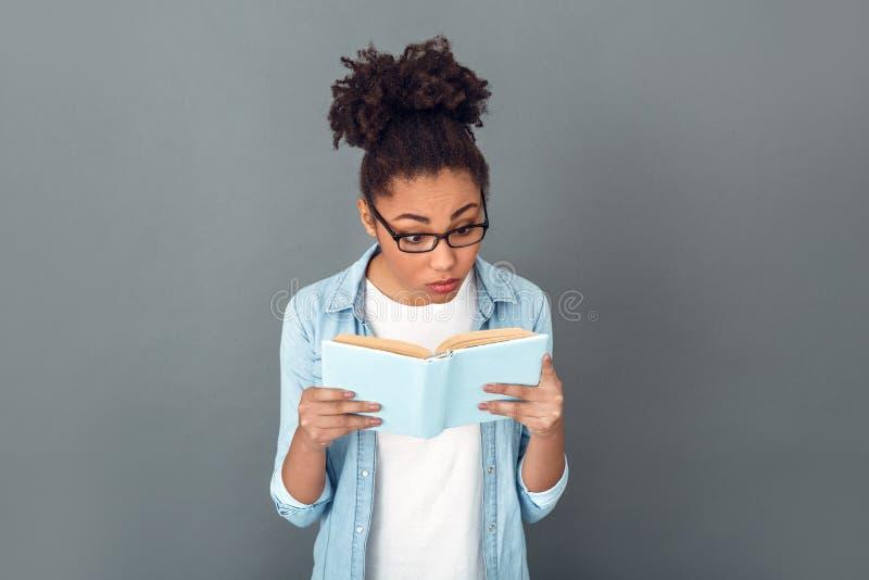 Młoda afrykańska kobieta odizolowywająca na popielatego ściennego pracownianego przypadkowego dziennego stylu życia studenckiej c fotografia royalty free