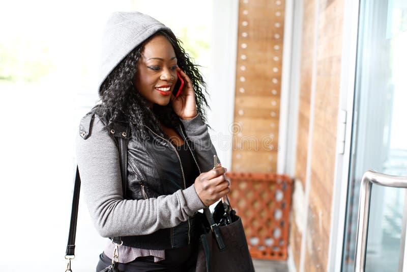 Młoda Afrykańska kobieta opowiada na telefonie komórkowym fotografia stock