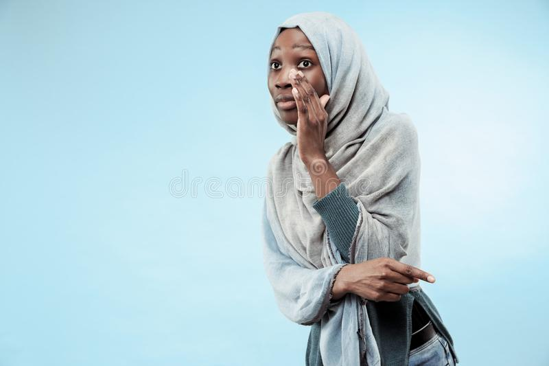 Młoda afrykańska kobieta szepcze sekret za ona oddaje błękitnego tło obraz royalty free