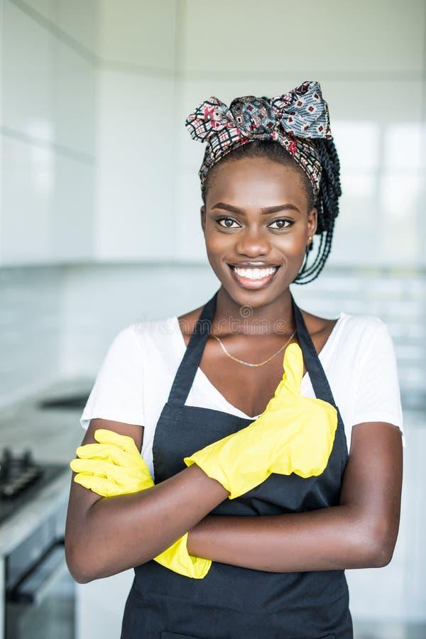 Młoda afrykańska kobieta w żółtych rękawiczkach pokazuje kciuk w górę w domu który obraz stock