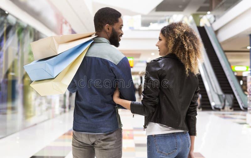 Młoda afrykańska para patrzeje each inny z papierowymi torbami fotografia royalty free