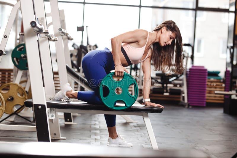 Młoda ahletic brunetki dziewczyna ubierająca w sportswear robi ćwiczeniom dla plecy z talerzem na ławce w nowożytnym obraz royalty free
