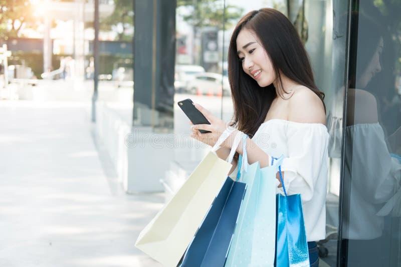 Młoda aisin kobieta używa jej smartphone i chwyta torba na zakupy whi fotografia royalty free