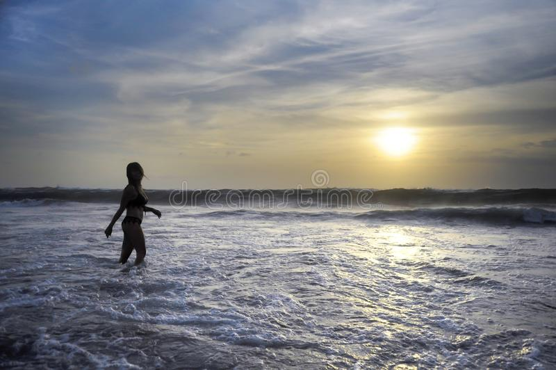 Młoda aktywna kobieta na morze krajobrazu zmierzchu horyzoncie z zadziwiającym słońcem i dramatycznym pomarańczowym niebem zdjęcie stock