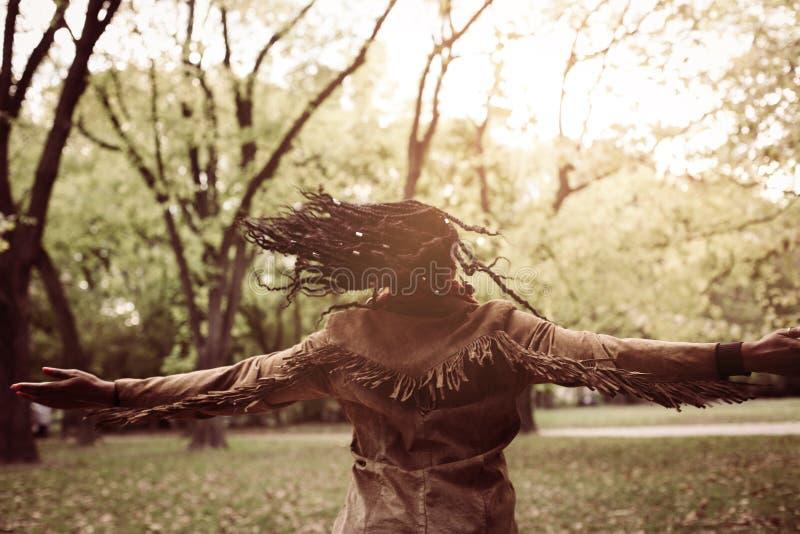 Młoda amerykanin afrykańskiego pochodzenia dziewczyna cieszy się w jesień dniu w parkowym dancingowym dowcipie zdjęcie royalty free