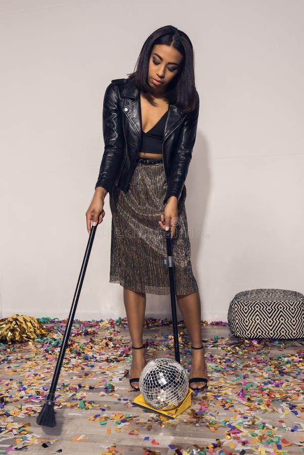 młoda amerykanin afrykańskiego pochodzenia dziewczyna sprząta w górę confetti z pył tacą fotografia stock
