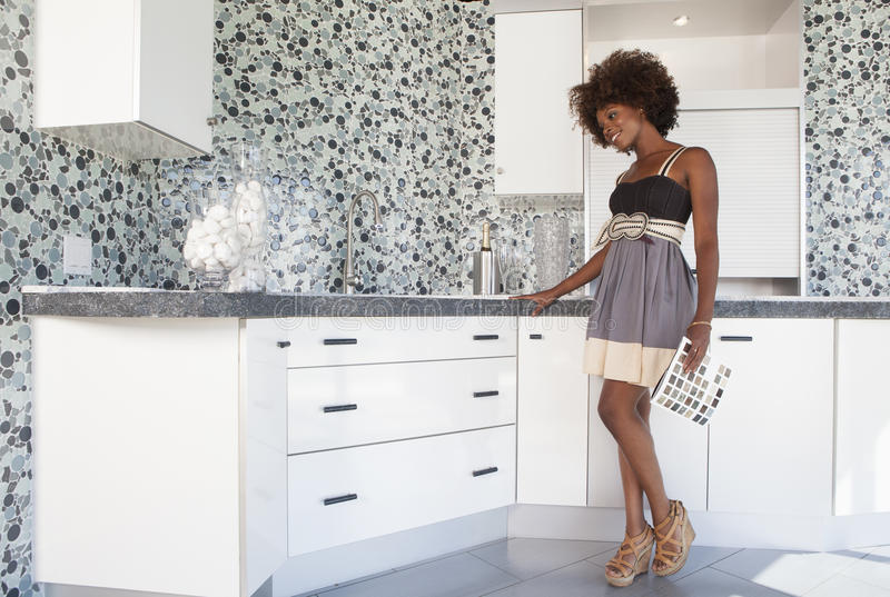 Młoda amerykanin afrykańskiego pochodzenia dziewczyna wybiera materiały w nowej meblującej kuchni zdjęcie stock