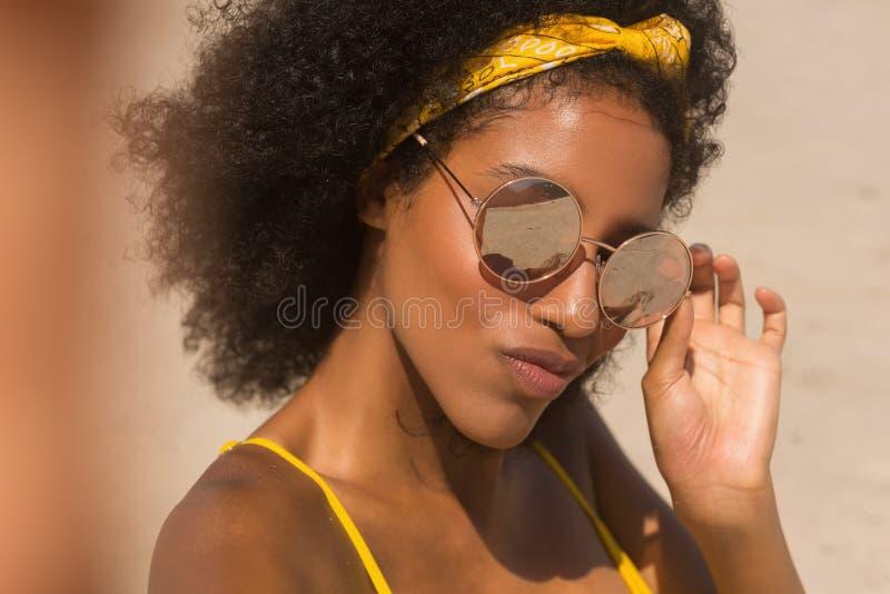 Młoda amerykanin afrykańskiego pochodzenia kobieta patrzeje kamerę na plaży w żółtym bikini i okularach przeciwsłonecznych zdjęcie stock