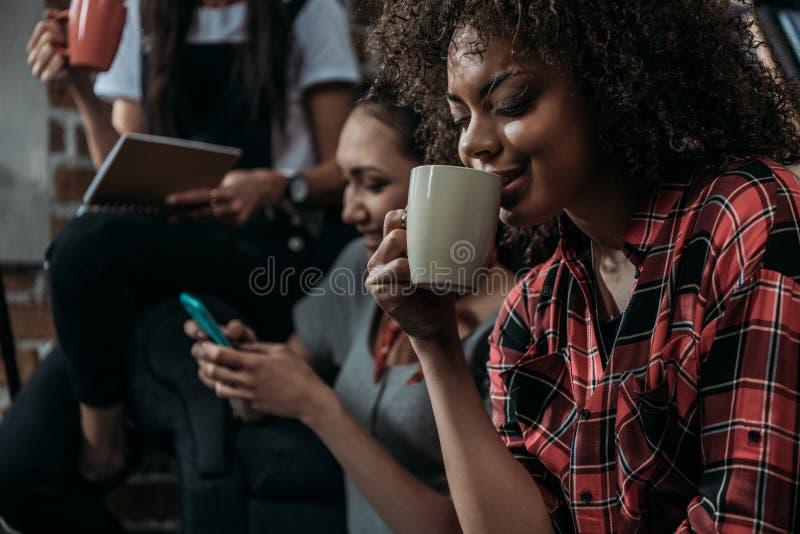 Młoda amerykanin afrykańskiego pochodzenia kobieta pije kawę podczas gdy przyjaciele używa smartphone i trzymający filiżankę behi zdjęcie stock