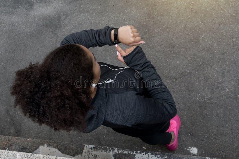 Młoda amerykanin afrykańskiego pochodzenia kobieta sprawdza aktywność tropiciela obrazy stock