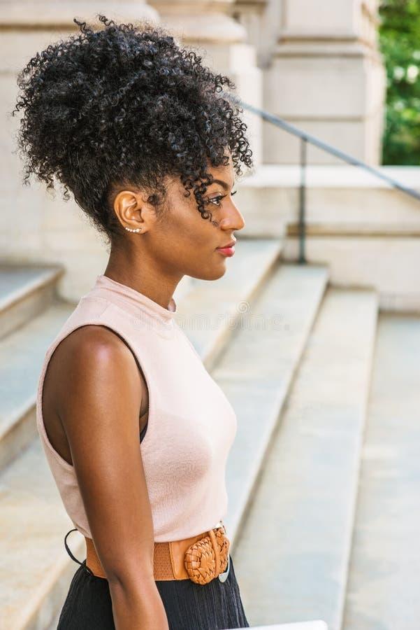 Młoda amerykanin afrykańskiego pochodzenia kobieta z afro fryzurą, biała uszata koralik szpilka, jest ubranym sleeveless lekkiego fotografia stock