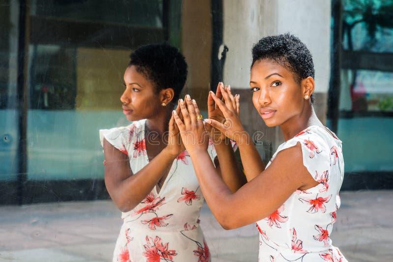 Młoda amerykanin afrykańskiego pochodzenia kobieta z krótką afro fryzurą, stoi obraz royalty free