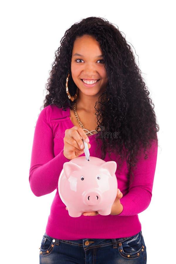 Młoda amerykanin afrykańskiego pochodzenia kobiety kładzenia moneta w prosiątko banku obraz royalty free