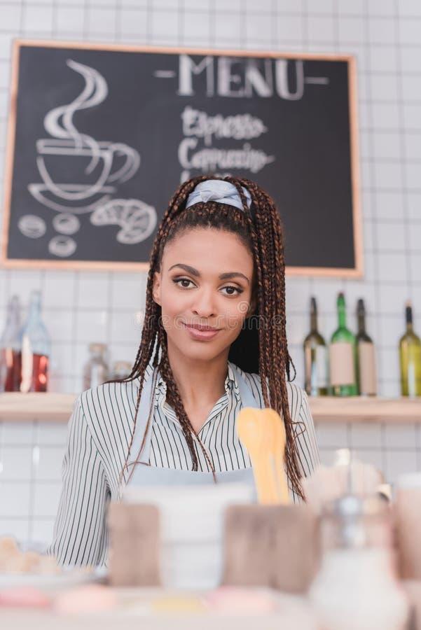 Młoda amerykanina afrykańskiego pochodzenia barista pozycja za kontuarem zdjęcie royalty free