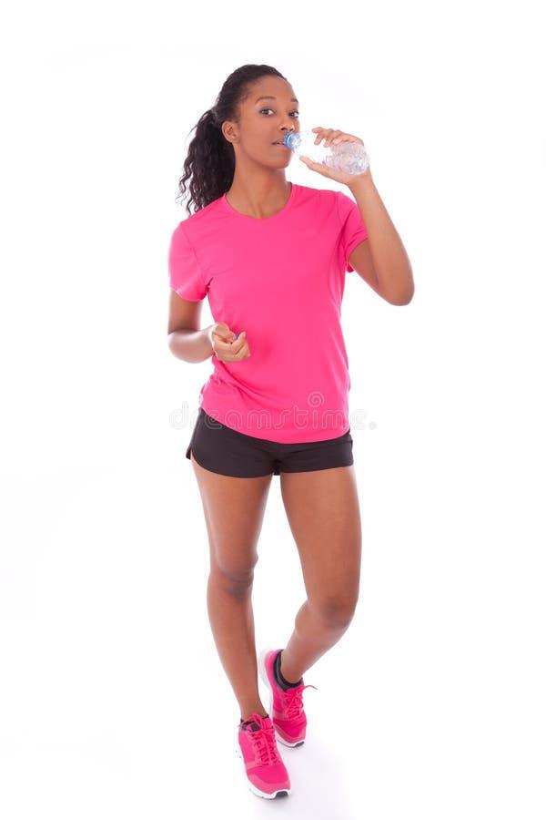Młoda amerykanina afrykańskiego pochodzenia jogger kobiety woda pitna, odizolowywająca dalej fotografia stock