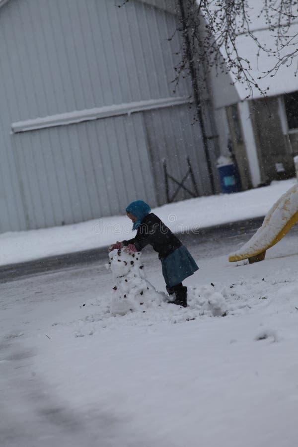 Młoda Amish dziewczyna buduje bałwanu obrazy stock
