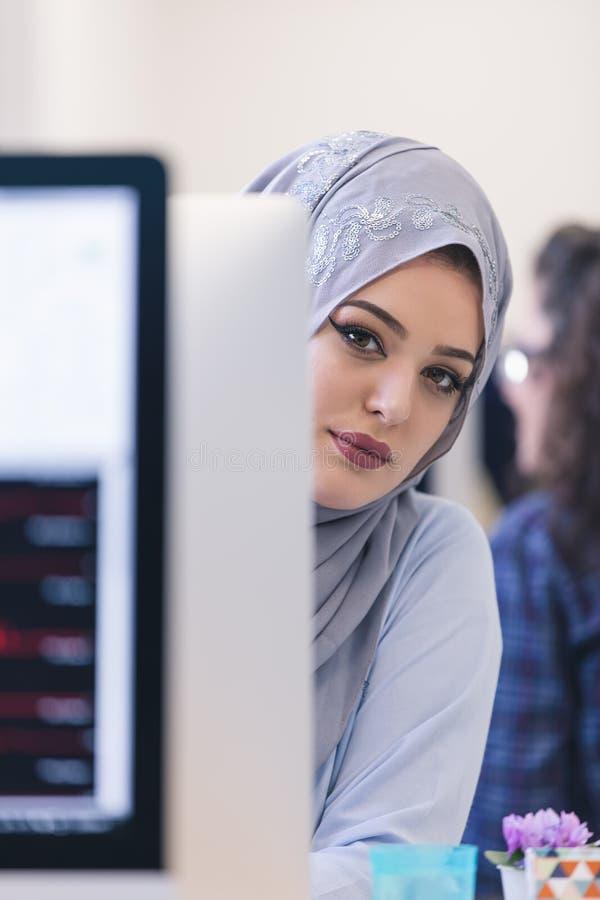 Młoda Arabska biznesowa kobieta jest ubranym hijab, pracuje w jej rozpoczęciu obrazy stock