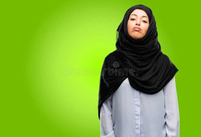 Młoda arabska kobieta jest ubranym hijab odizolowywającego nad zielonym tłem fotografia royalty free