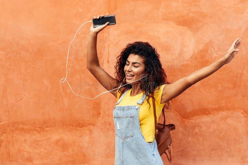 Młoda Arabska kobieta słucha muzyka z słuchawkami outdoors obraz royalty free
