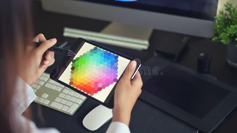 Młoda artystka twórcza projektowania stron WWW, pracująca nad wyborem kolorów na tablecie graficznym obraz royalty free