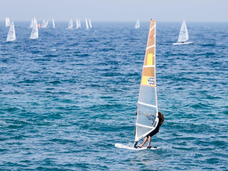 Młoda atleta ćwiczy w windsurfing w morzu śródziemnomorskim w Nahariya w czarnym tracksuit, Izrael zdjęcie royalty free