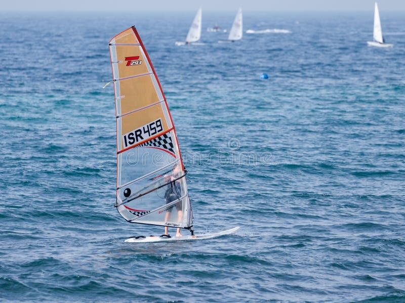 Młoda atleta ćwiczy w windsurfing w morzu śródziemnomorskim w Nahariya w czarnym tracksuit, Izrael fotografia royalty free