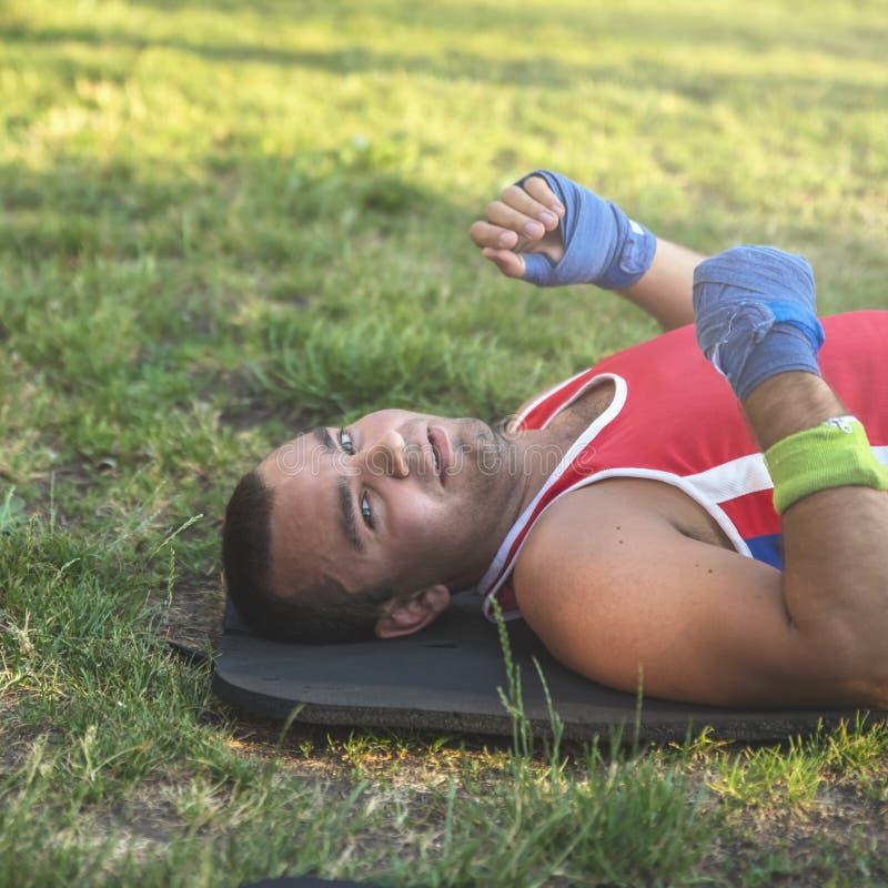 Młoda atleta kłama na jego plecy na trawie podczas fermaty na a zdjęcia royalty free