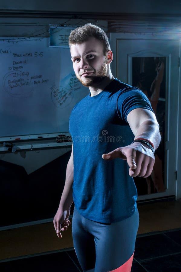 Młoda atleta stoi przy gym i wskazuje przed on obraz stock