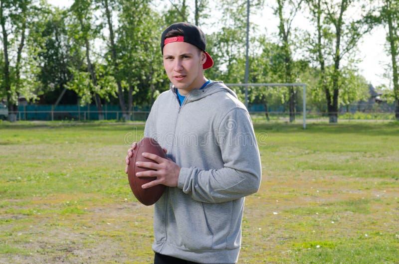 Młoda atleta trzyma futbolową piłkę fotografia stock