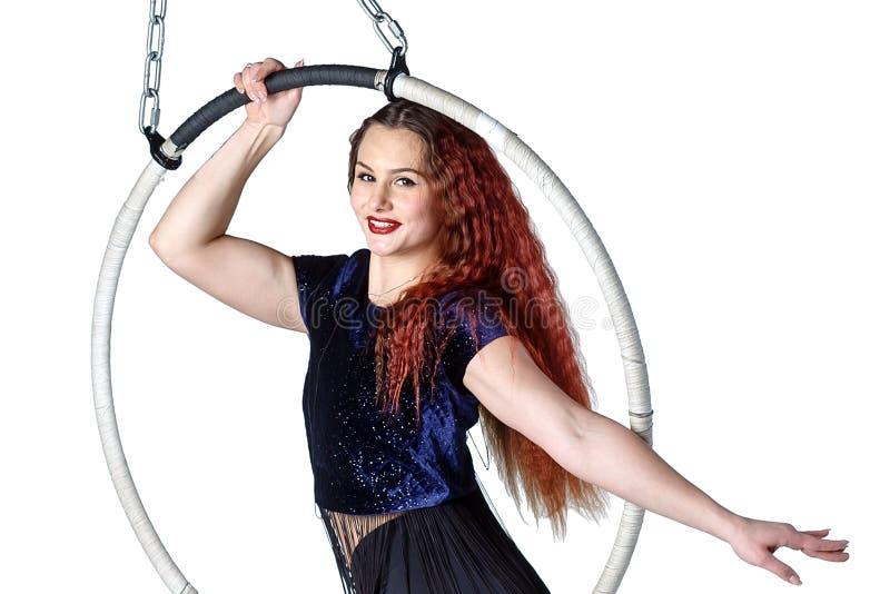 Młoda atrakcyjna akrobatyczna kobieta siedzi w okręgu zdjęcia royalty free