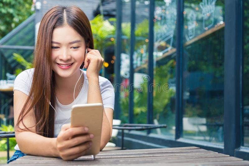 Młoda atrakcyjna azjatykcia kobieta siedzi plenerowego l w przypadkowych ubraniach obrazy stock