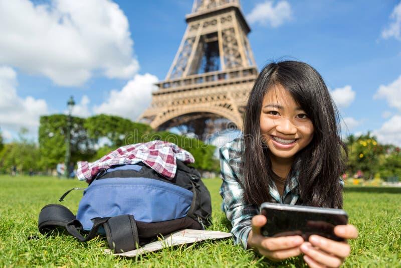 Młoda atrakcyjna azjatykcia turystyczna smartphone pastylka w Paryż fotografia royalty free