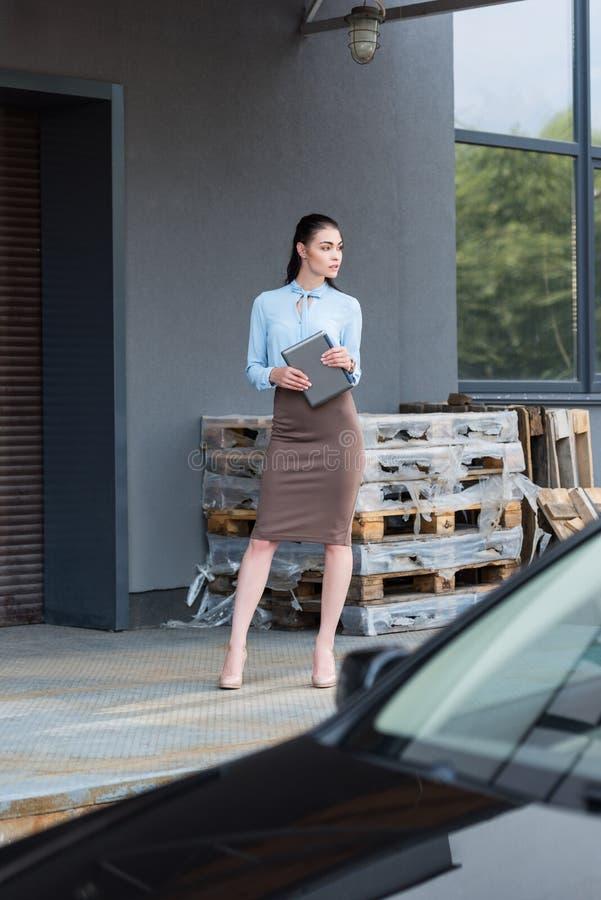 Młoda atrakcyjna bizneswoman pozycja na zewnątrz przemysłowego budynku a i mienia fotografia stock