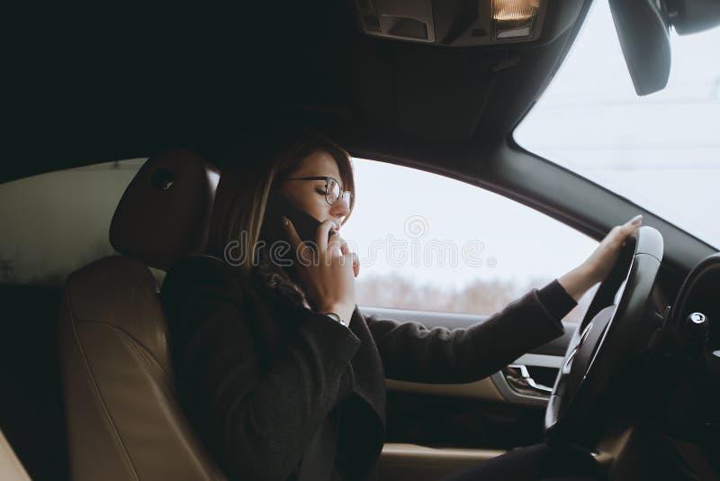 Młoda atrakcyjna blondynka używa telefon w samochodzie podczas gdy siedzący fotografia stock