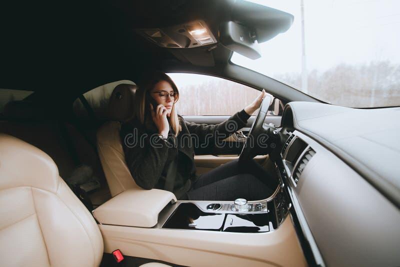 Młoda atrakcyjna blondynka używa telefon w samochodzie podczas gdy siedzący zdjęcia stock