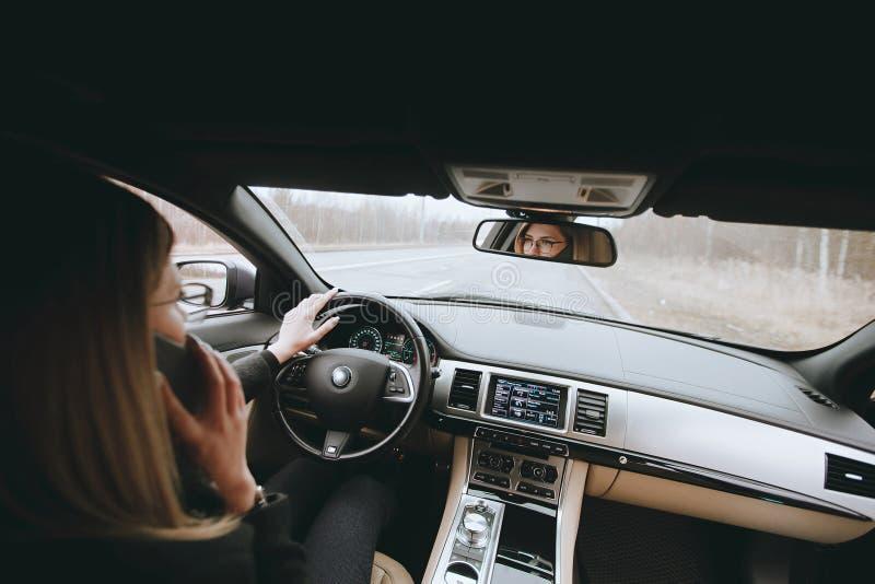 Młoda atrakcyjna blondynka używa telefon w samochodzie podczas gdy siedzący fotografia royalty free