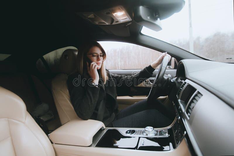 Młoda atrakcyjna blondynka używa telefon w samochodzie podczas gdy siedzący Styl życia i samochody obrazy stock