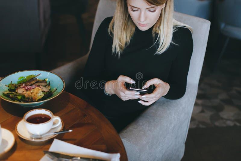 Młoda atrakcyjna blondynki kobieta używa telefon przy gościem restauracji w restauracji obraz stock