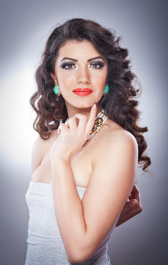 Młoda atrakcyjna brunetki dama z makeup i piękną fryzurą pozuje na popielatym tle w studiu zdjęcie stock