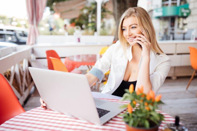 Młoda atrakcyjna dziewczyna opowiada na telefonie komórkowym i ono uśmiecha się podczas gdy siedzący samotnie w sklep z kawą podc zdjęcie royalty free
