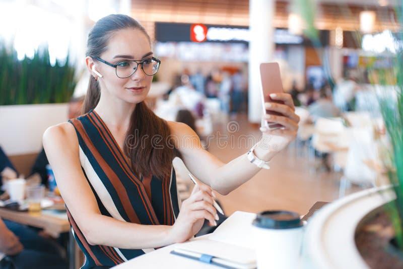Młoda atrakcyjna dziewczyna w szkłach robi selfie używać telefon w kawiarni fotografia royalty free