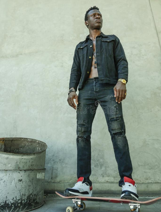 Młoda atrakcyjna i poważna czarna afro Amerykańska mężczyzna jazdy łyżwy deska przy grunge rogu ulicego przyglądający chłodno poz zdjęcia stock