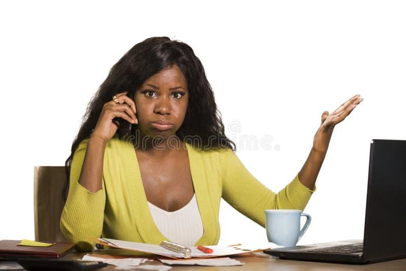 Młoda atrakcyjna i ruchliwie czarna afro Amerykańska biznesowa kobieta pracuje biurowego komputeru biurko opowiada na telefonie s fotografia royalty free