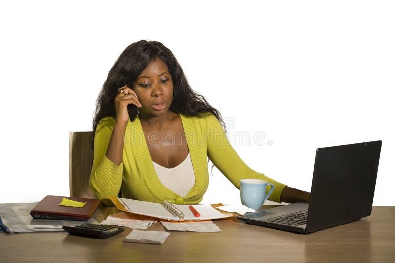 Młoda atrakcyjna i ruchliwie czarna afro Amerykańska biznesowa kobieta pracuje biurowego komputeru biurko opowiada na telefonie s zdjęcia royalty free