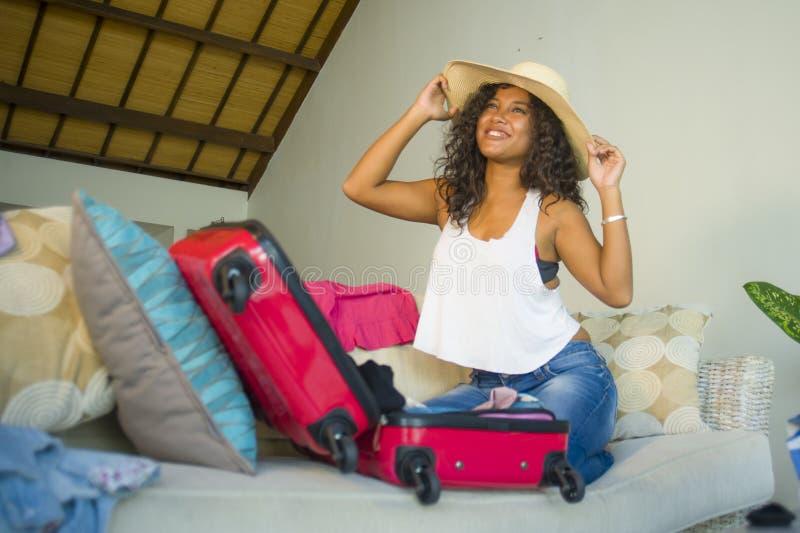 Młoda atrakcyjna i szalona szczęśliwa czarna afro Amerykańska kobieta w plażowego lata narządzania kapeluszowej walizce opuszcza  zdjęcia stock