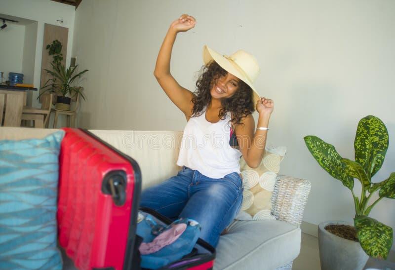 Młoda atrakcyjna i szalona szczęśliwa czarna afro Amerykańska kobieta w plażowego lata narządzania kapeluszowej walizce opuszcza  zdjęcie stock