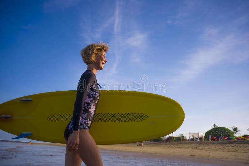 Młoda atrakcyjna i szczęśliwa blondynka surfingowa dziewczyna w pięknego plażowego przewożenia kipieli deski żółtym odprowadzeniu obrazy royalty free