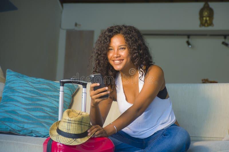 Młoda atrakcyjna i szczęśliwa czarna afro Amerykańska kobieta z walizką używa telefon komórkowego opuszcza dla wakacji w domu ono fotografia royalty free