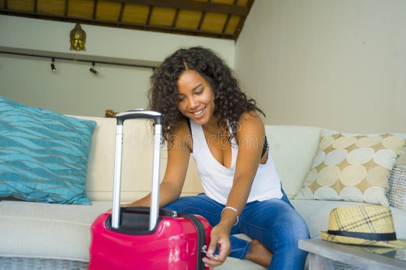 Młoda atrakcyjna i szczęśliwa czarna latyno-amerykański kobieta z walizki obsiadaniem na kanapy leżance opuszcza dla wakacji w do obraz royalty free