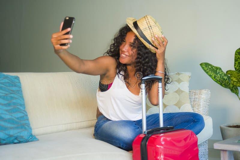 Młoda atrakcyjna i szczęśliwa czarna latyno-amerykański kobieta z walizki obsiadaniem na kanapy leżance opuszcza dla wakacji w do zdjęcie royalty free